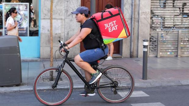 ep fotografia de un repartidor de la empresa de reparto just eat transitando en bicicleta por una