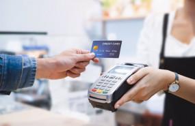 ep una persona pagando con tarjeta de credito en un datafono de un comercio