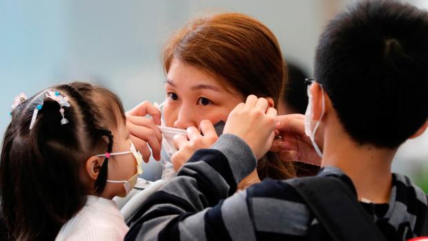 femme-ajuste-masque-pour-prevenir-declenchement-nouveau-coronavirus-chine
