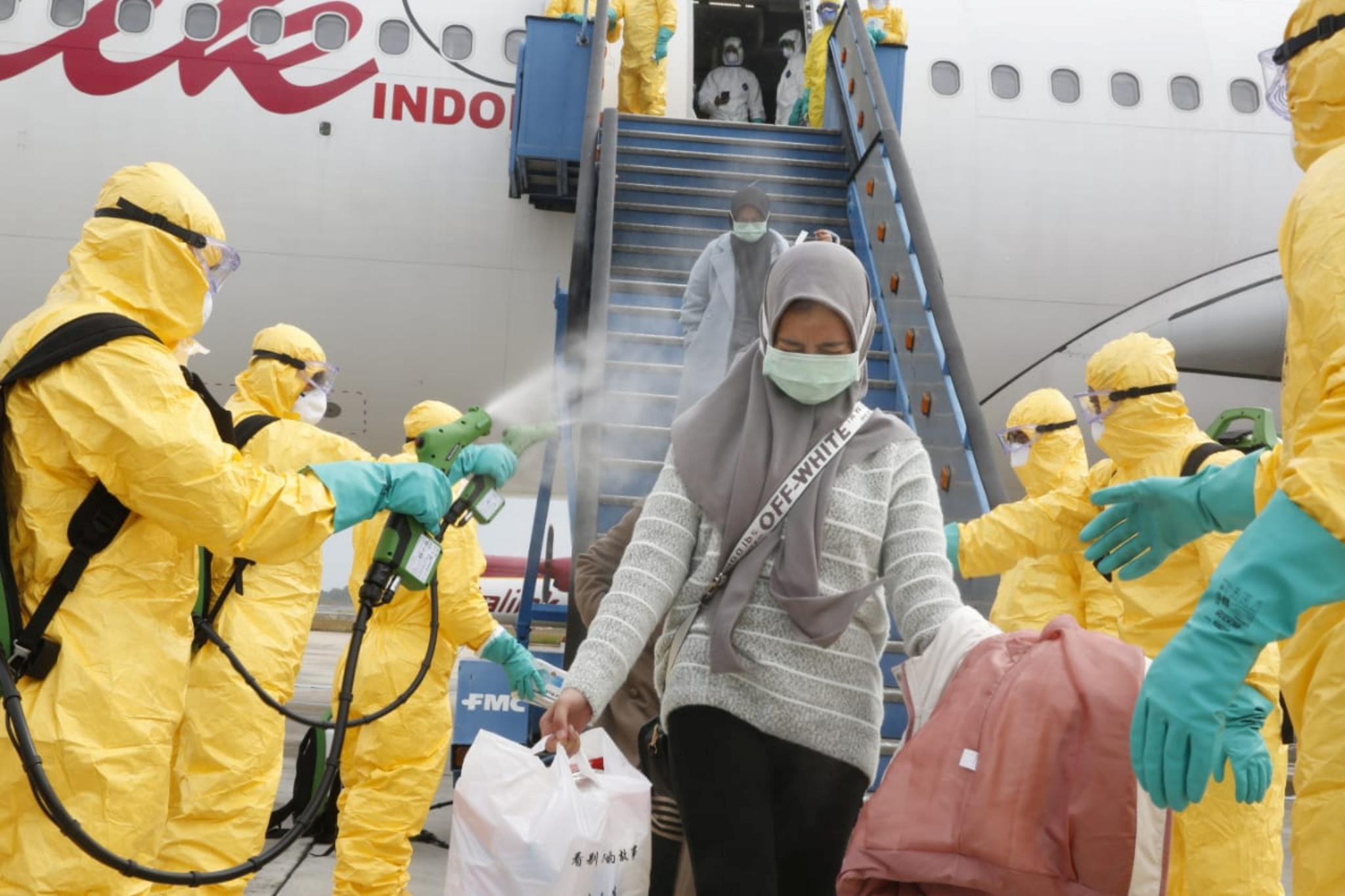 coronavirus-covid-19-des-medecins-diffusent-un-spray-antiseptique-sur-une-femme-rapatriee-de-chine-en-indonesie-le-2-fevrier-2020 20200215103817